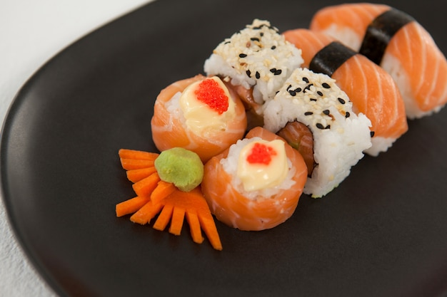 Maki, uramaki et nigiri sushi servi dans une assiette noire sur fond blanc
