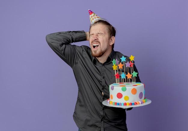 Mal bel homme dans le chapeau d'anniversaire tient la tête derrière et tient le gâteau isolé sur le mur violet
