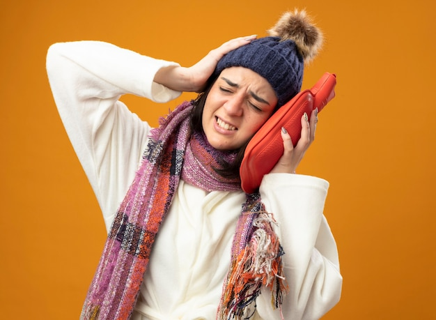 Mal jeune fille malade caucasienne portant chapeau d'hiver robe et écharpe toucher la tête avec un sac d'eau chaude en gardant la main sur la tête avec les yeux fermés isolé sur un mur orange avec espace copie