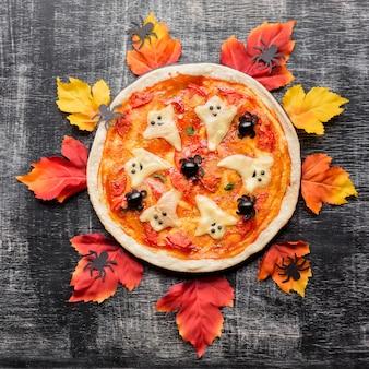 Mal pizza d'halloween entouré de feuilles