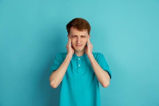 Mal de tête, bouleversé. portrait moderne du jeune homme caucasien isolé sur mur bleu, monochrome. beau modèle masculin.