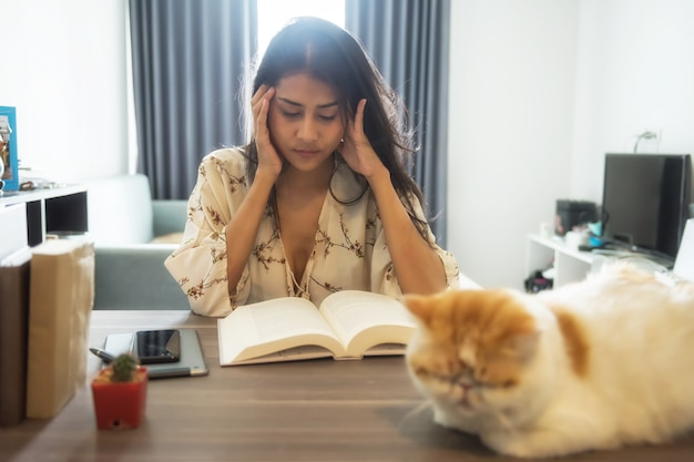 Mal de tête femme lire le livre pour l'examen final
