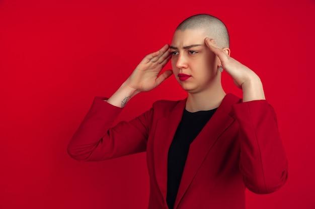 Mal de tête, problème. portrait de jeune femme chauve caucasienne isolée sur mur rouge. beau modèle féminin en veste. émotions humaines, expression faciale, ventes, concept publicitaire. culture bizarre.