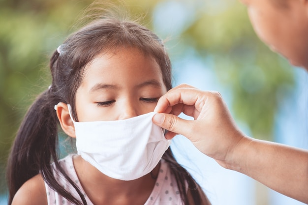 Malade asiat petite fille porter un masque de protection et la mère aider à fermer son nez