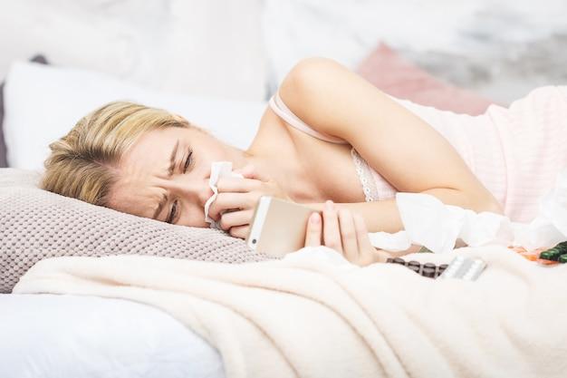 Malade belle femme couchée dans son lit avec une forte fièvre
