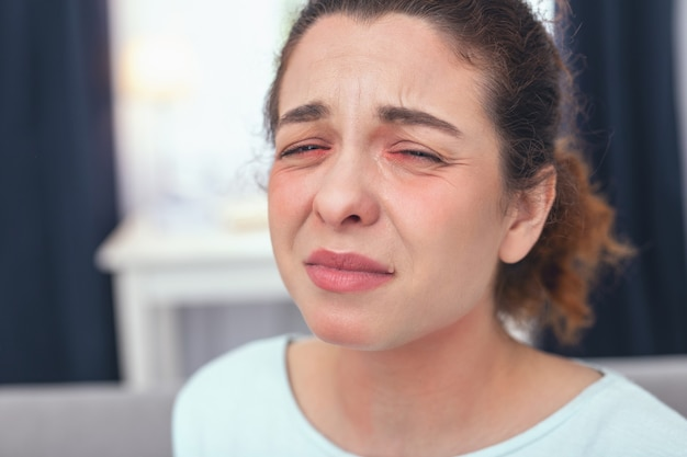 Malade et bouleversé. jeune femme à la recherche de malade fronçant les sourcils tout en souffrant de fièvre et de froid saisonnier