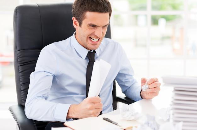 Malade et fatigué. jeune homme furieux en chemise et cravate tenant des papiers dans les mains et criant alors qu'il était assis sur son lieu de travail