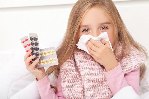 Malade fille sur lit éternuer dans mouchoir dans chambre à coucher