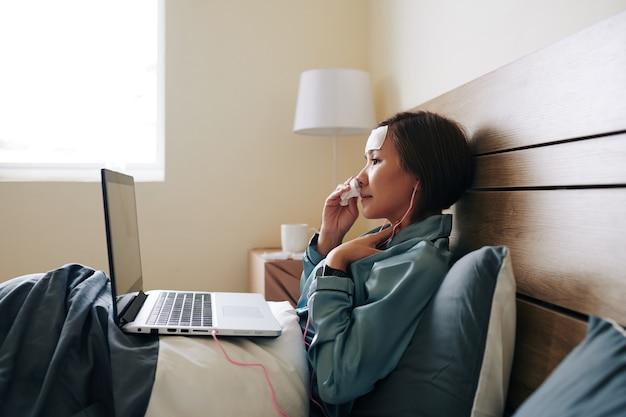 Malade jeune femme vietnamienne couchée dans son lit et vidéo appelant son médecin