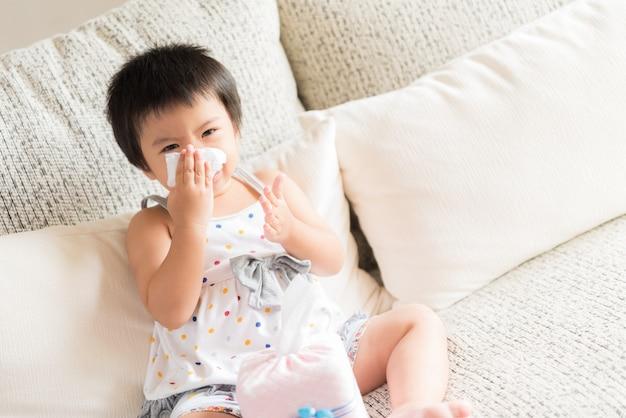 Malade petite fille asiatique essuyant ou nettoyant le nez avec des tissus