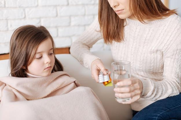 Malade petite fille gentille assise sous la couverture pendant que sa mère lui donne des pilules et aide à récupérer