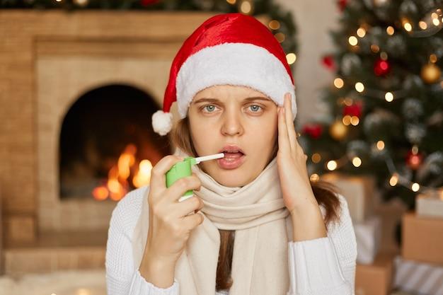 Malade pour la nouvelle année! triste femme malade en bonnet de noel et écharpe blanche assis près de l'arbre de noël et cheminée