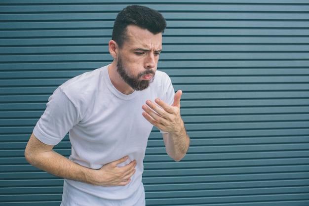 Un malade vomit. il essaie de l'empêcher. il tient une main sur le stomack et une autre près de la bouche. isolé sur rayé