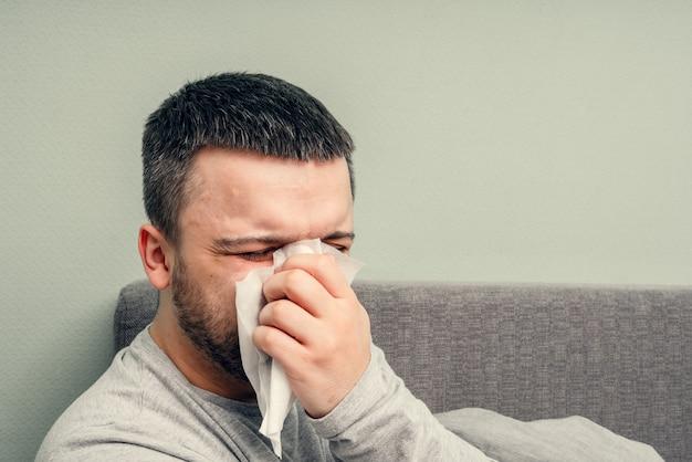 Maladie. bravo à la maison. un jeune homme est malade, est soigné à domicile. se mouche dans une serviette, nez qui coule. infection, épidémie, porteur de bacilles.