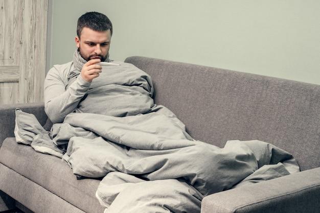 Maladie. bravo à la maison. un jeune homme est malade, est soigné à domicile. se mouche dans une serviette, nez qui coule. mesure de la température corporelle. infection, épidémie, porteur de bacilles. coronavirus