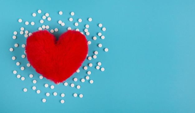 Maladie cardiaque concept. coeur rouge et comprimés blancs sur fond bleu