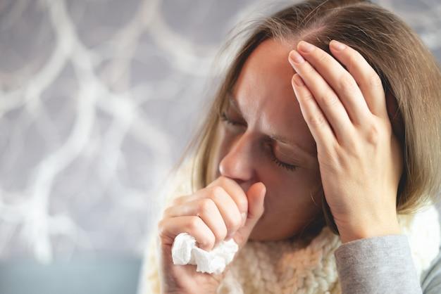 Maladie. traitement à domicile. une femme est malade à la maison, le nez qui coule et la grippe