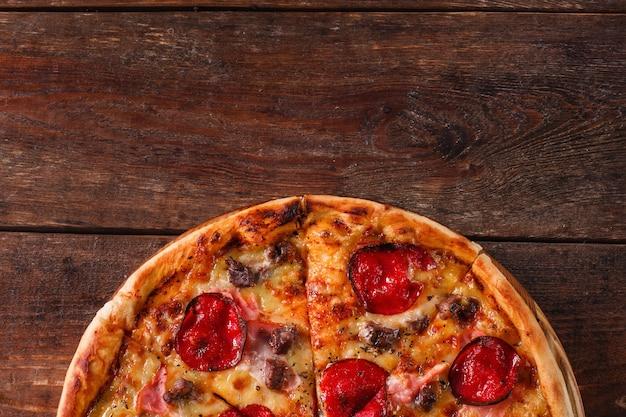 Malbouffe, mauvaises habitudes, calories. pizza fraîche au salami, bacon et fromage sur une table en bois rustique, mise à plat avec espace libre pour le texte.