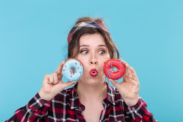 Malbouffe, régime alimentaire et concept de mode de vie malsain - femme pin-up avec des beignets sur fond bleu.