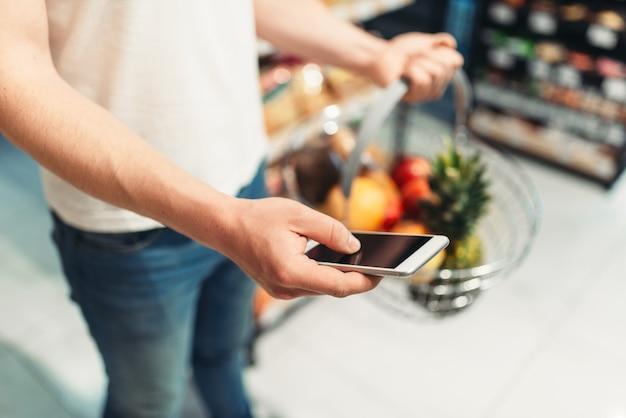 Mâle acheteur mains avec panier de fruits et téléphone