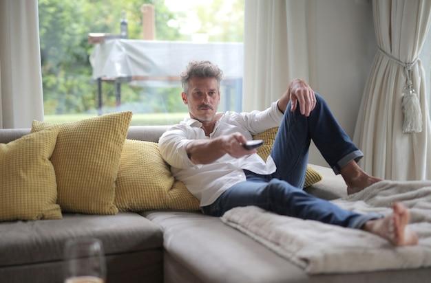 Mâle adulte allongé sur le canapé et tenant une télécommande sous la lumière du soleil à travers les fenêtres