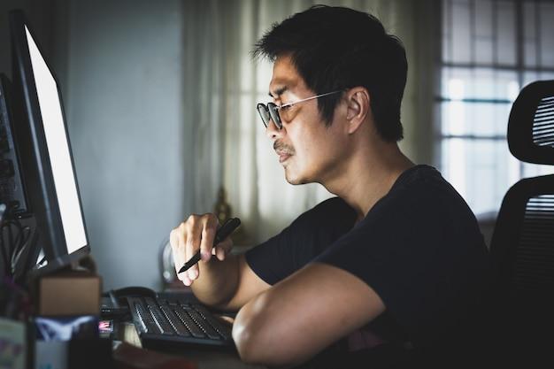 Mâle adulte avec des lunettes travaillant à domicile