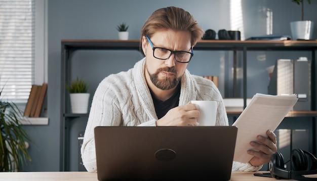 Mâle adulte occupé regardant écran d'ordinateur portable tenant des papiers et une tasse de travail à domicile
