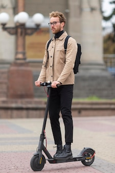 Mâle adulte posant avec un scooter électrique