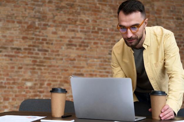 Mâle adulte en se concentrant sur son ordinateur portable