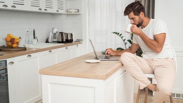 Mâle adulte travaillant à la maison avec désinvolture