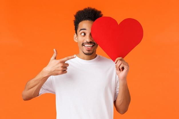 Mâle afro-américain en t-shirt blanc tenant coeur