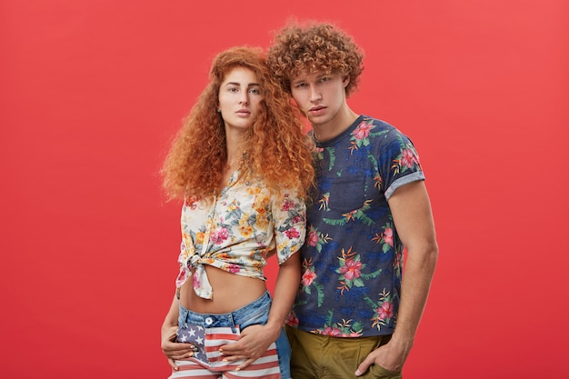 Mâle aux cheveux roux en t-shirt avec motif de fleurs debout près de jolie femme
