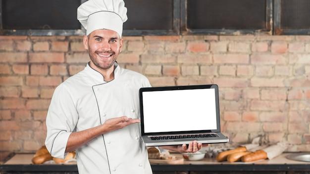 Male baker souriant montrant un ordinateur portable ouvert avec écran blanc vierge