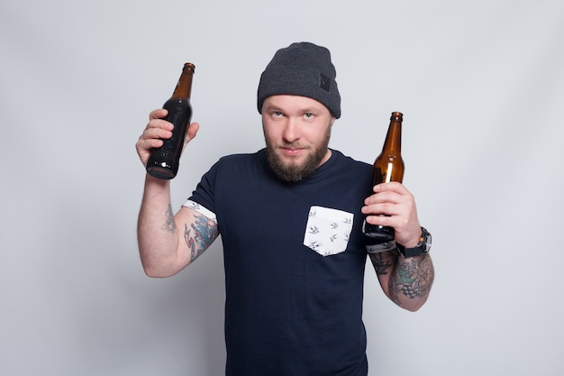 Mâle barbu brutal avec bras tatoué boit une bière d'une bouteille