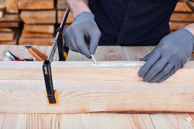 Mâle charpentier mains à l'aide de colle à bois et de bois sur une table en bois pour des meubles faits à la main.