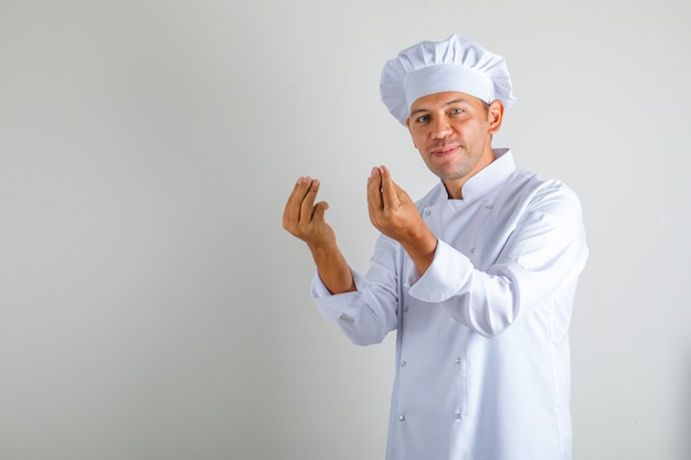 Mâle chef cuisinier en chapeau et uniforme faisant le geste italien avec les doigts