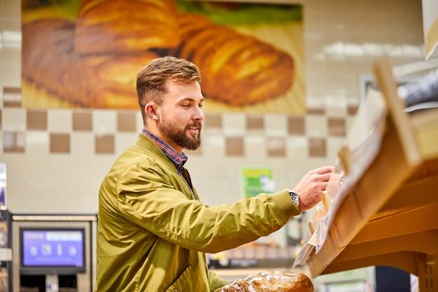 Mâle choisissant du pain au supermarché, beau mec en cavalier regarde la boulangerie fraîche en magasin, veulent l'acheter