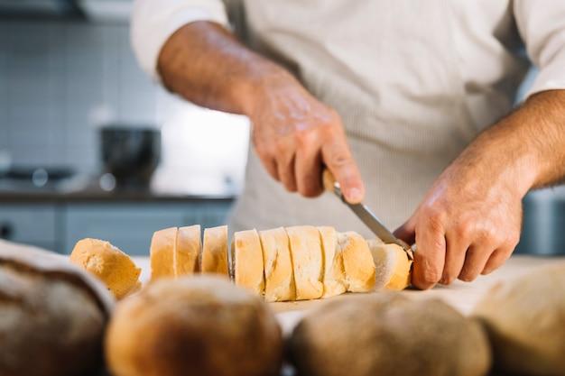 Mâle couper du pain avec un couteau sur le comptoir de la cuisine