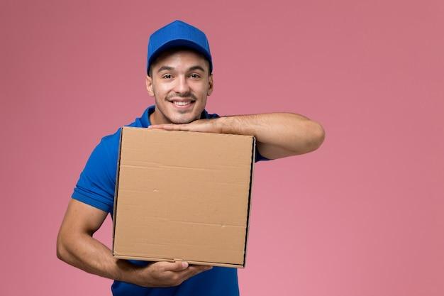 Mâle courrier en uniforme bleu tenant la boîte de livraison de nourriture et souriant sur rose, prestation de services uniforme de travailleur de l'emploi