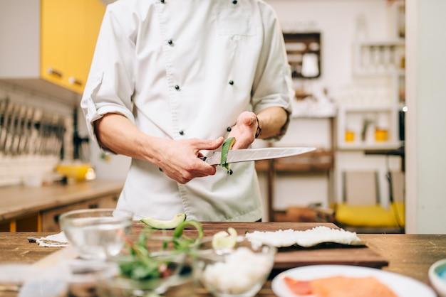 Mâle cuisinier mains gros plan, faisant des rouleaux de sushi