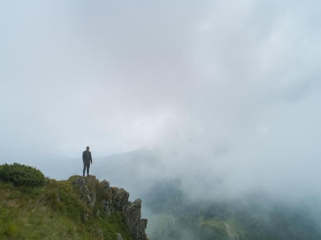 Le mâle debout sur la montagne brumeuse