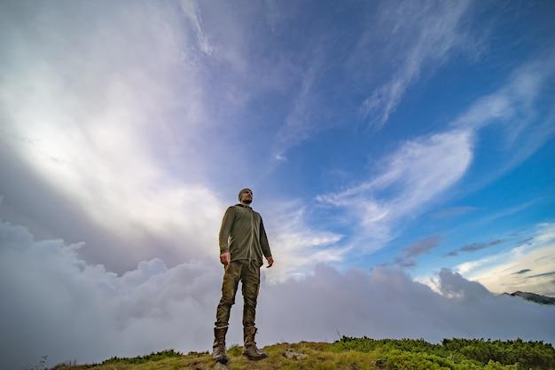 Le mâle debout sur la montagne sur un fond de ciel nuageux