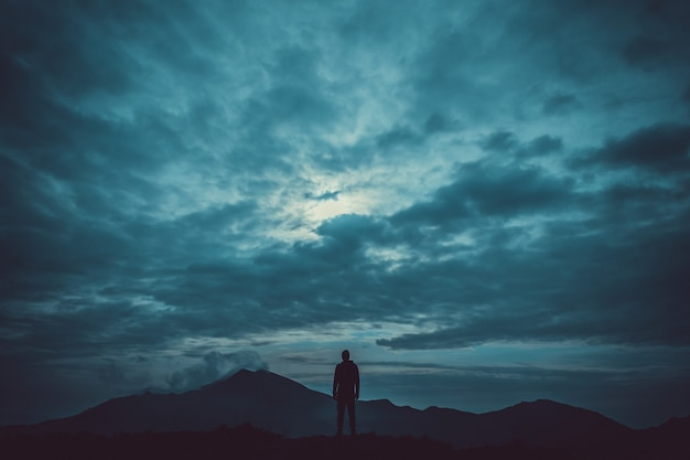 Le mâle debout sur la montagne sur fond de nuage
