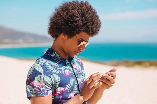 Mâle ethnique en regardant smartphone sur la plage de sable fin