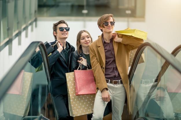 Mâle et femelle shopper sur escalator dans le centre commercial