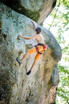 Mâle grimpeur escalade avec une corde sur un mur rocheux