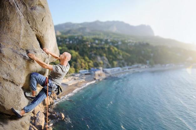 Mâle grimpeur escalade gros rocher dans la nature avec une corde