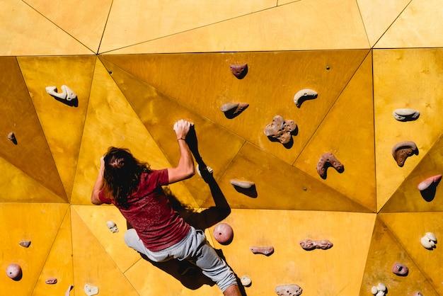 Mâle grimpeur essayant un itinéraire compliqué au soleil sur un mur d'escalade en plein air