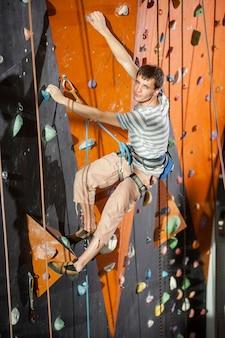Mâle grimpeur pratiquant l'escalade sur la paroi rocheuse à l'intérieur
