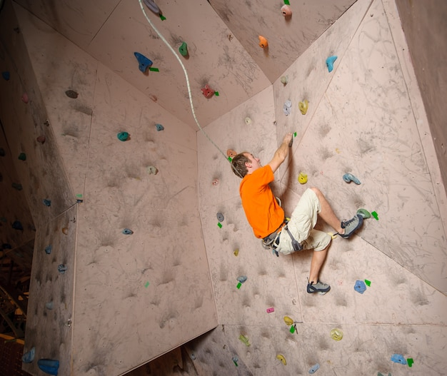 Mâle grimpeur pratiquant l'escalade sur une paroi rocheuse à l'intérieur